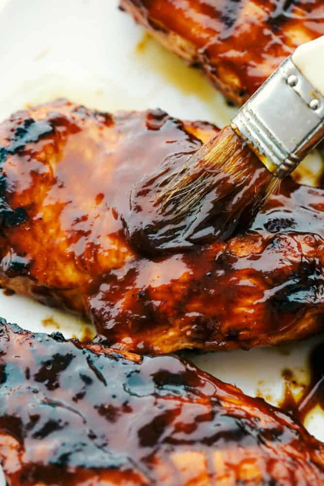 Brushing barbecue sauce on grilled chicken.