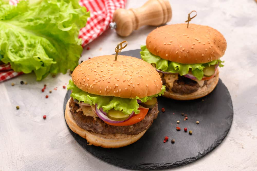Two large hamburgers on a large black plate.