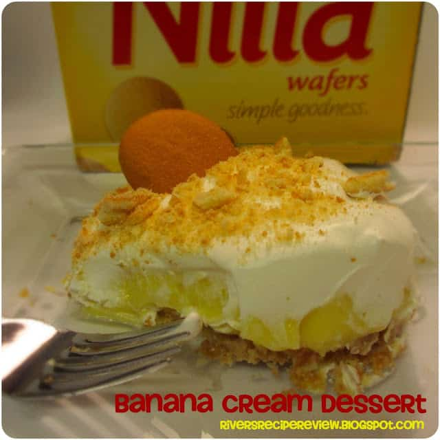 Nilla Wafers Banana Cream Dessert on a clear plate with a metal fork and a box of Nilla Waffers in the background.