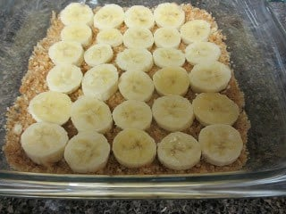 Sliced banana nicely aligned on crushed Nilla Wafer base in a clear baking pan.