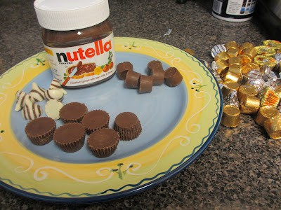 Herseys Kisses, small Reeses cups, Rolos and Nutella on a festive plate.