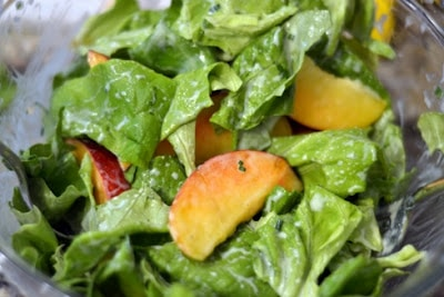 Salad greens with slices of peach.