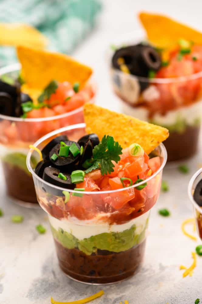 Individual cups with seven layers of refried beans, guacamole, sour cream and topped with tomatoes, black olives, scallions and a chip.