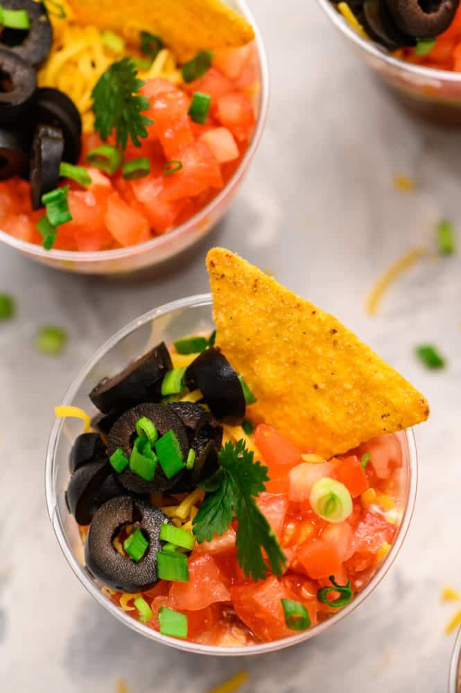 A photo of the individual cup with black olives, tomatoes, scallions and a chip.