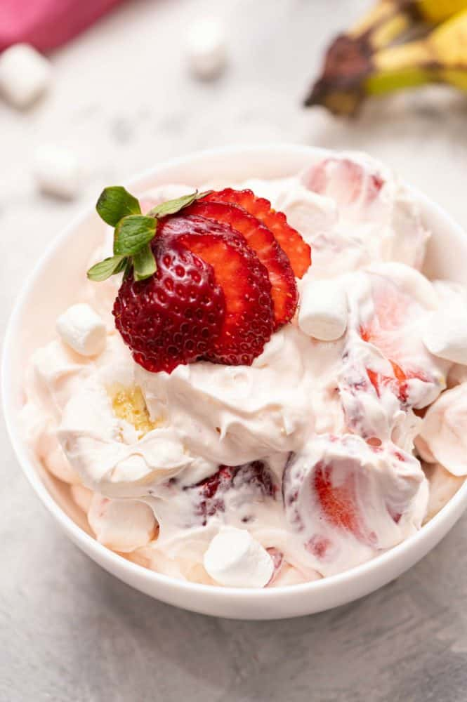 Close up of Strawberry Cheesecake Salad in a white bowl with fresh cut strawberries on top.