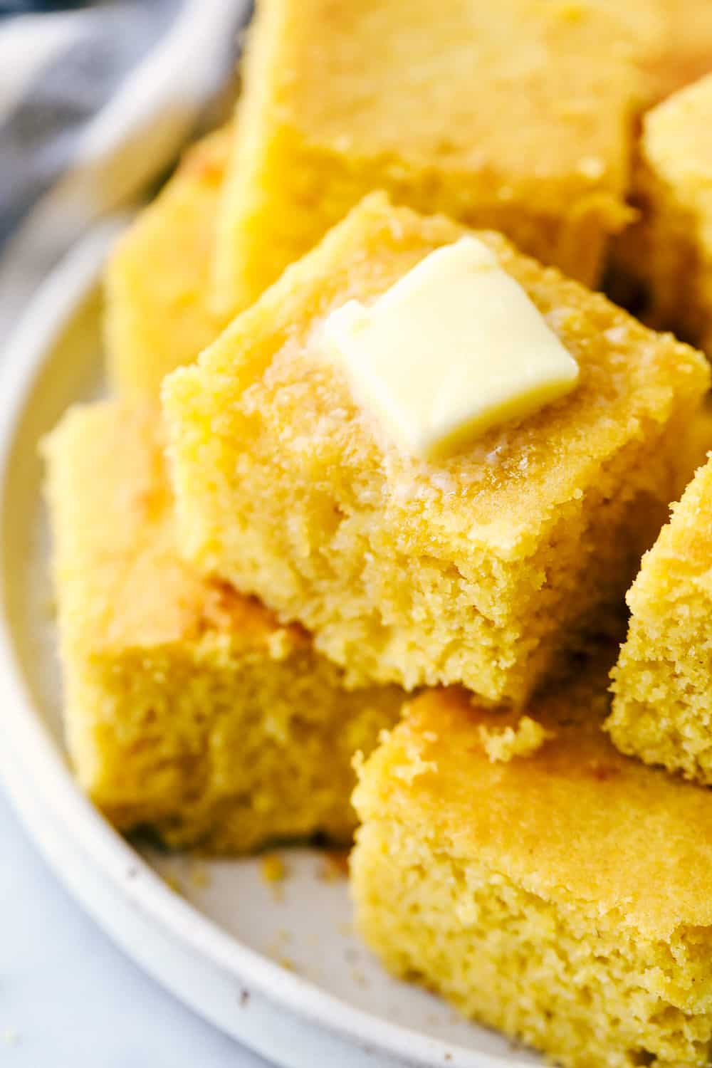 Cornbread cut into squares and stacked with a slice of butter on top.