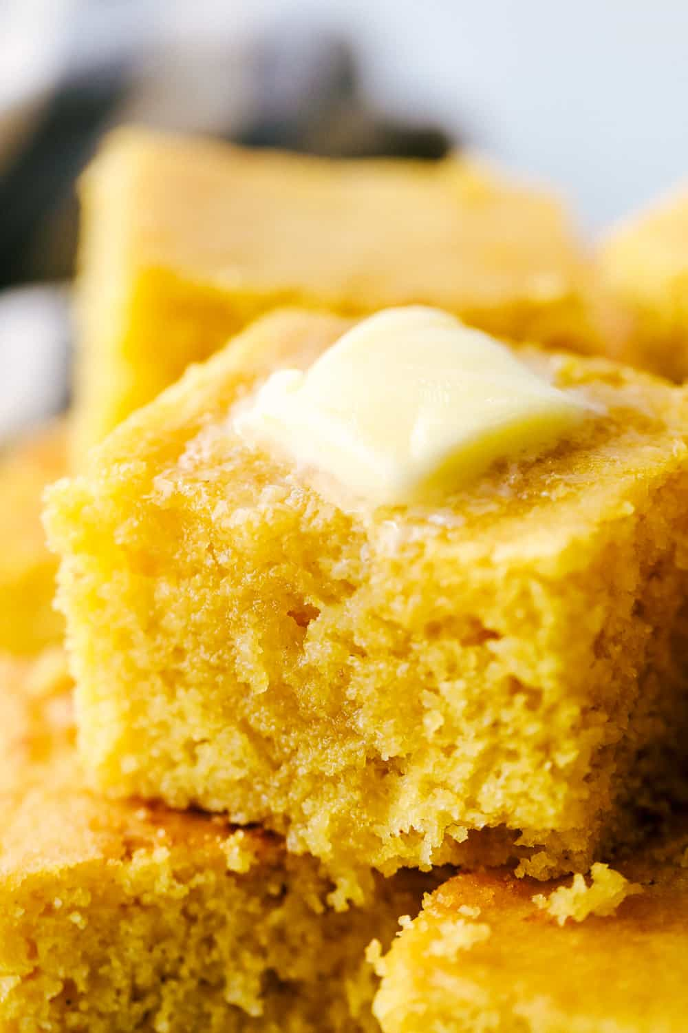 Close up on cornbread with butter on top.