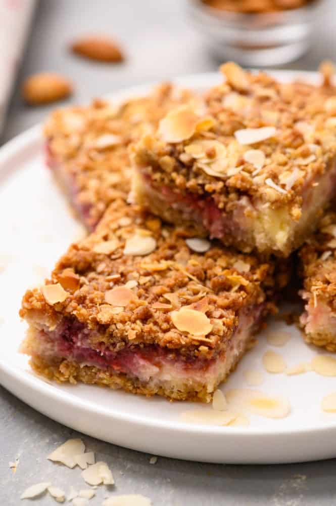 Raspberry cheesecake bars stacked on top of each other on a white plate.
