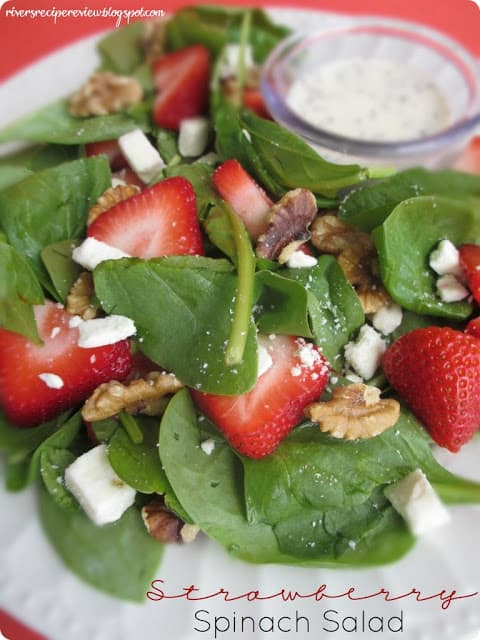 Strawberry Spinach Salad on a white plate with some dressing in a small dish.