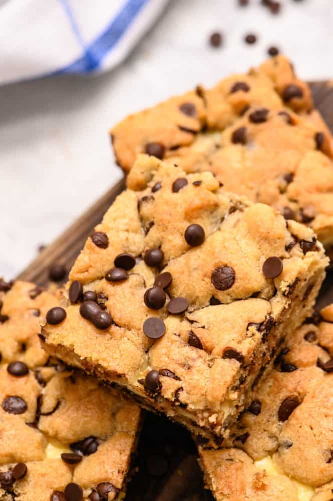 Chocolate chip cheesecake brownies stacked on top of each other.