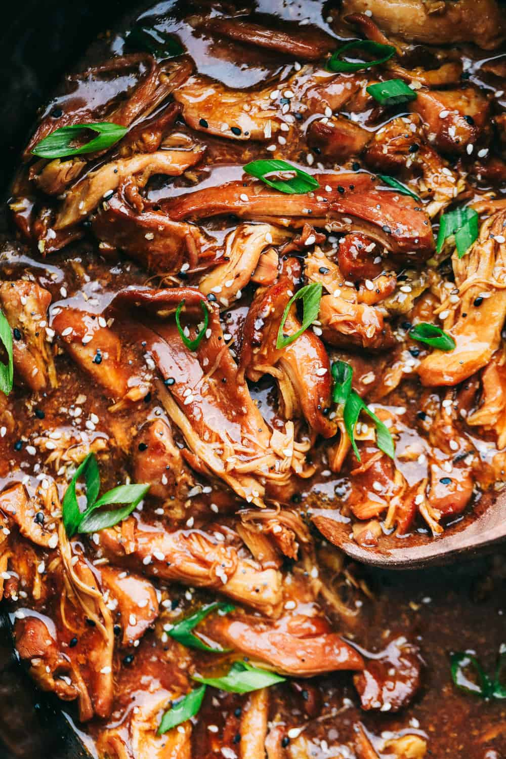 Honey garlic chicken in a slow cooker with a wooden spoon stirring it up.