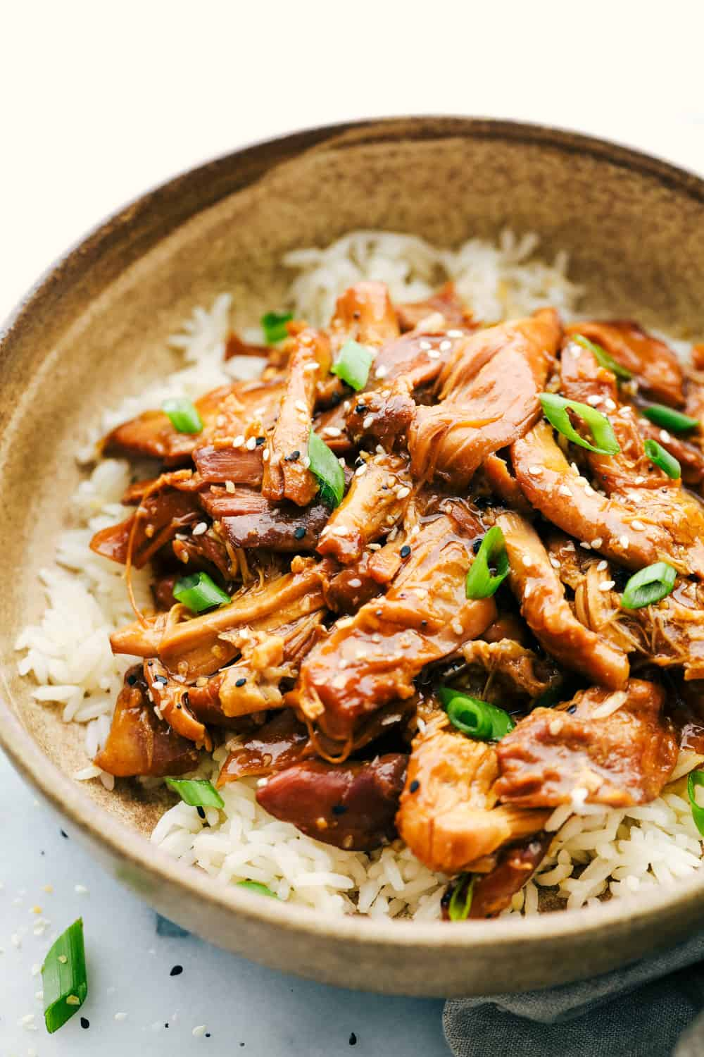 Honey garlic chicken in a bowl with rice and garnished with scallions.