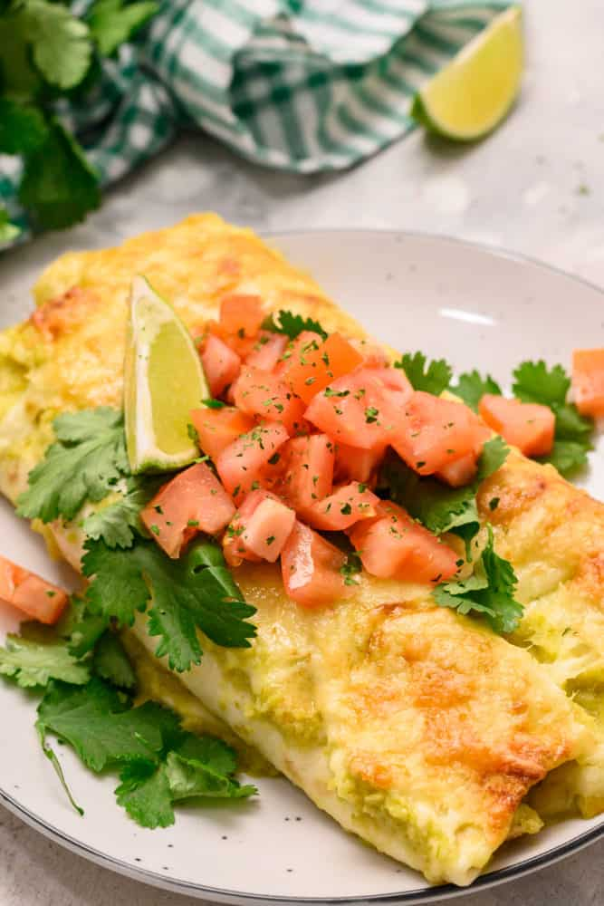 Honey lime chicken enchiladas on a plate with chopped tomatoes and cilantro garnished on top.