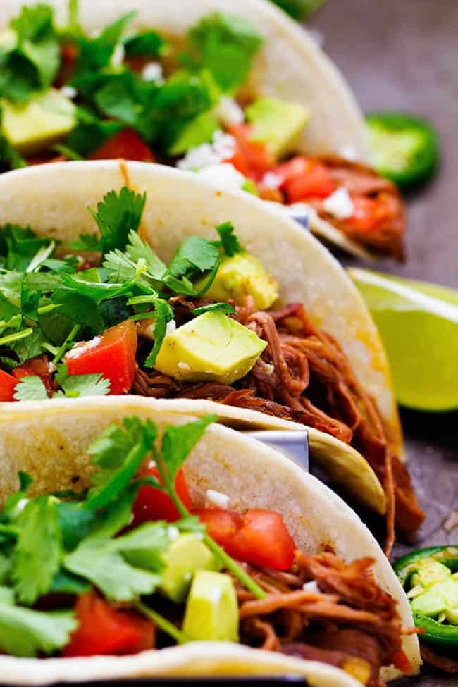 Slow cooker beef carnitas with cilantro on top and limes on the side.