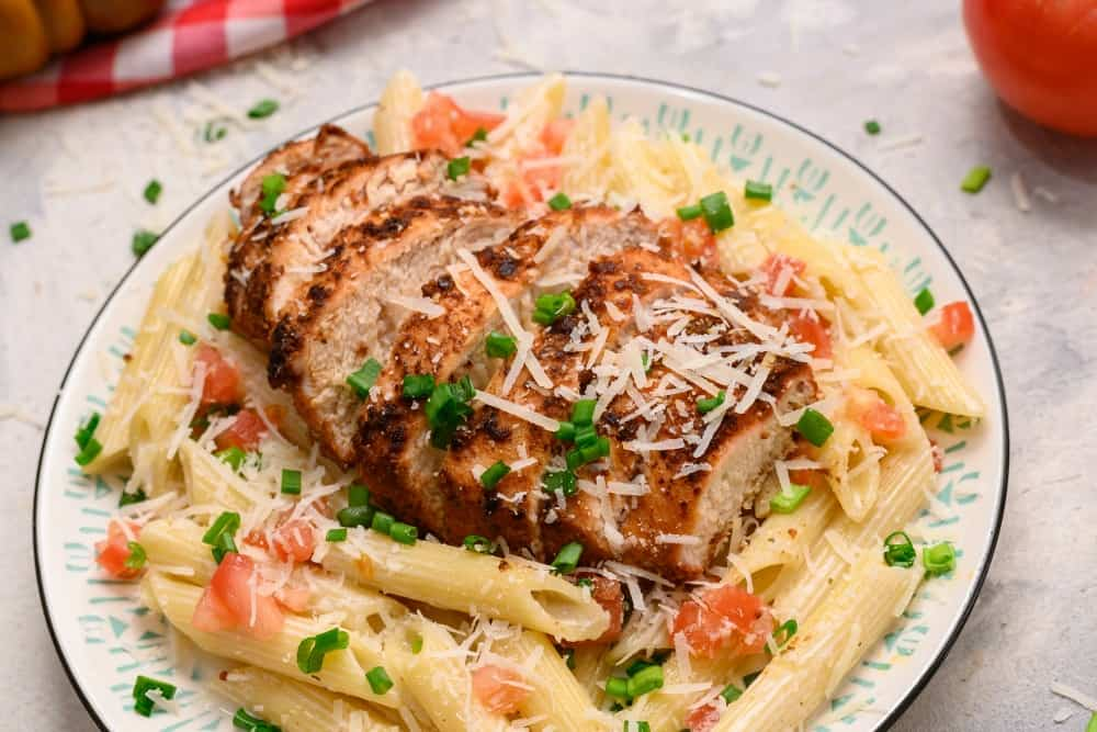 Cajun chicken pasta on a plate garnished with shredded parmesan.