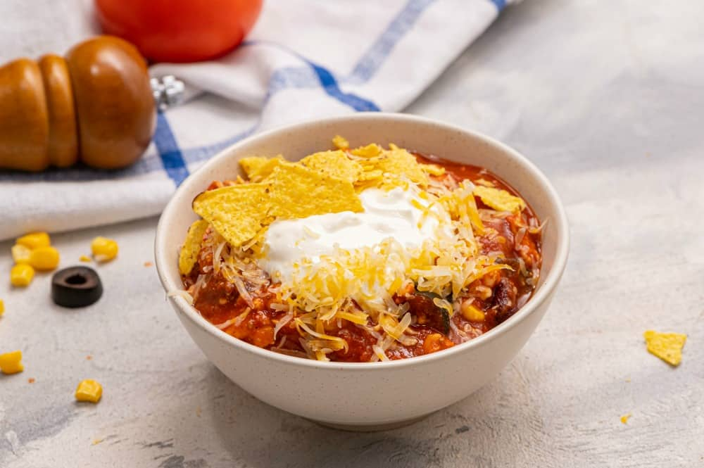 Skinny taco soup in a white bowl garnished with tortilla chips and shredded cheese.