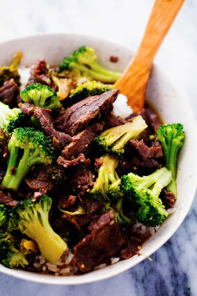 Close up on slow cooker beef and broccoli in a white bowl with a wooden spoon.