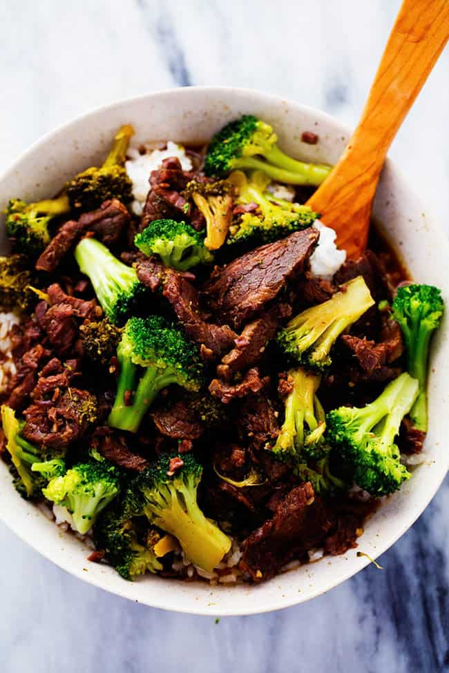 Slow cooker beef and broccoli in a white bowl with a wooden spoon on the side.