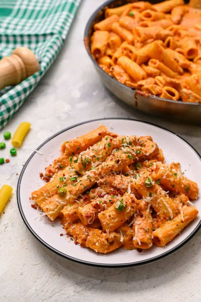 Spicy chicken rigatoni on a white dish with the skillet behind in the photo.