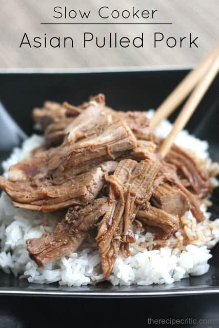 Slow cooker asian pulled pork served over white rice and on a black plate.