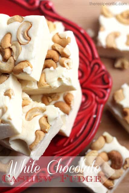 White chocolate cashew fudge stacked on top of each other on a red plate.