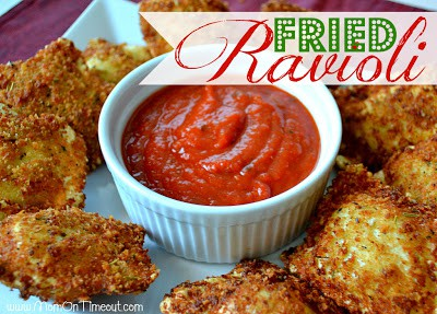 Fried Ravioli on a white square plate with a white cup of red sauce in the middle.