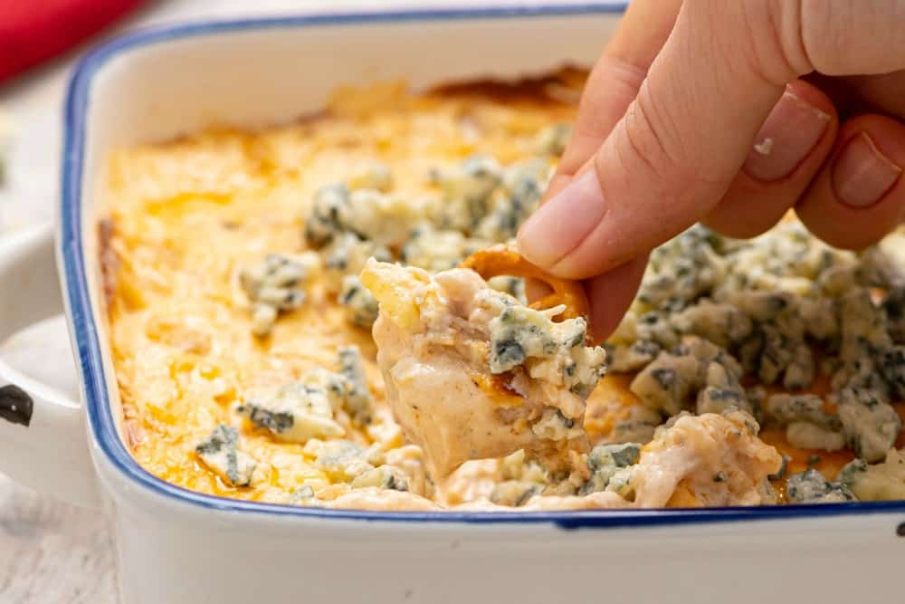 A hand with a chip in it is dipping some of the buffalo dip out of a blue and white dish.