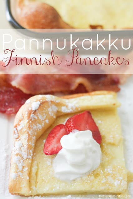 A Pannukakku Finnish pancake garnished with whipped creame and two slices of strawberries with bacon on the side.