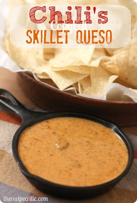 Chilli's skillet queso in a black cast iron skillet with a brown bowl of chips beside it.