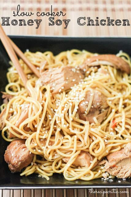 Slow cooker honey soy chicken in noodles with chopsticks and seasoned with sesame seeds all in a black bowl.