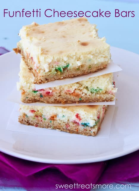 3 funfetti cheesecake bars stacked on top of each other with a white square paper between each. They are sitting on a white plate.