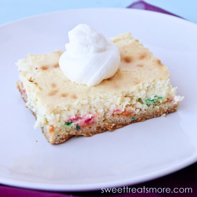 On funfetti cheesecake square with a dollup of whipped cream on top, sitting on a round white plate.