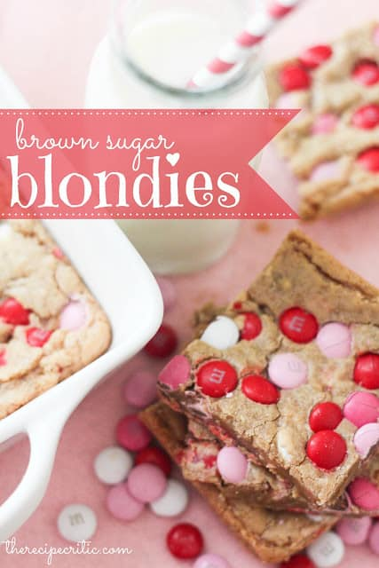 A stack of brown sugar blondies with pink, white, and red m and m's sit beside a glass of milk with a red and white striped straw and another brownie and a white pan of brownies.