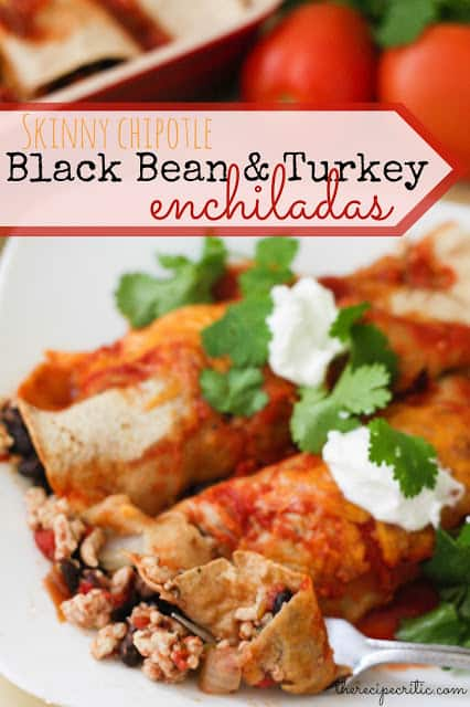 2 black bean and turkey enchiladas lay on a white plate garnished with cilantro and sour cream.