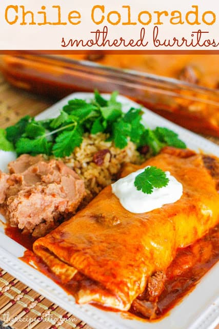 Chile Colorado Smothered Burritos with beans and rice on white plate