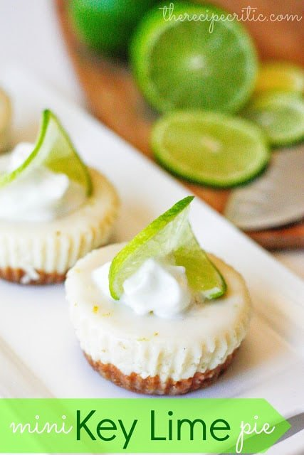 Two mini key lime pies on a white plate and garnished with a sliver of lime and a dollop of whipped cream on top.