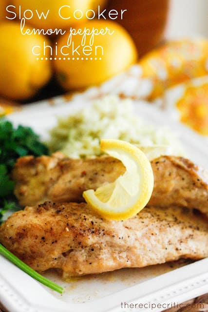 Slow Cooker Lemon Pepper Chicken on white plate with lemons in the background.