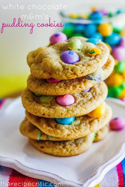 White chocolate M&Ms Pudding Cookies stacked on white plate
