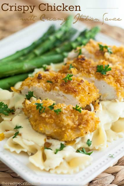Crispy chicken with creamy italian sauce on a white plate with pasta and asparagus.