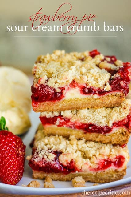 Strawberry Pie sour cream crumb bars in a stack of 3 beside a scoop of vanilla ice cream and a strawberry.