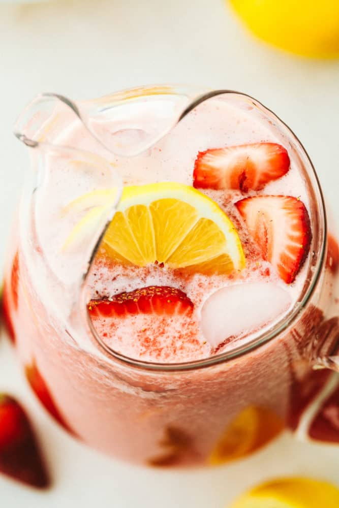 A top photo overview of a pitcher with homemade strawberry lemonade garnished with fresh cut lemons and strawberries.