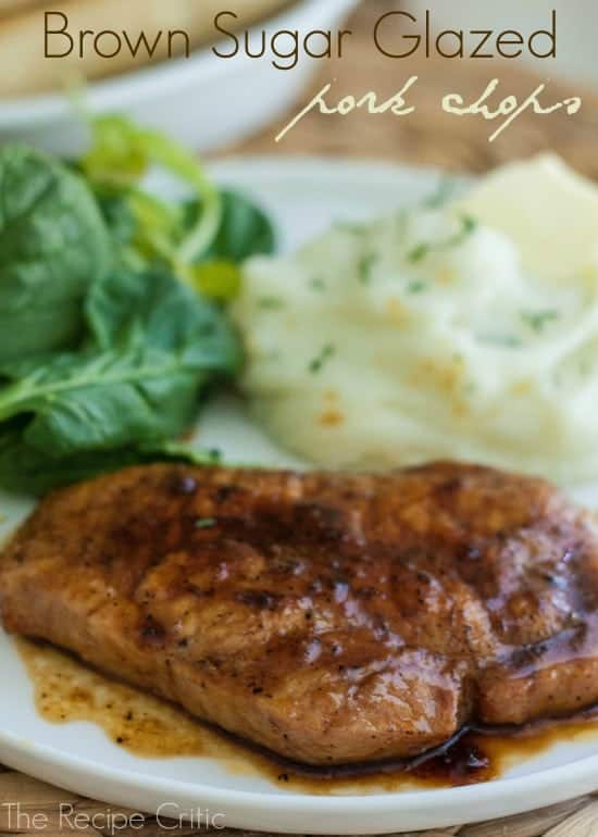 Brown sugar glazed pork chops with mashed potatoes and a green salad on a white plate.