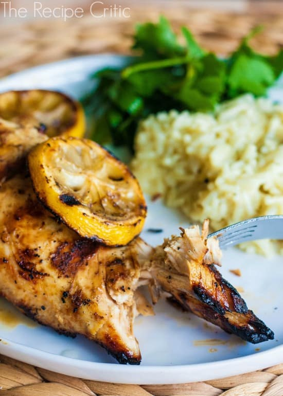 Grilled lemon chicken with 2 grilled lemons on top on a white plate.