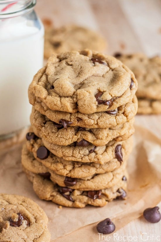 Stack of 7 chocolate chip cookies beside a glass jar of milk.
