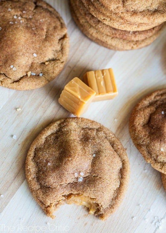 Snickerdoodle cookies on a wooden counter with 2 caramel candies.