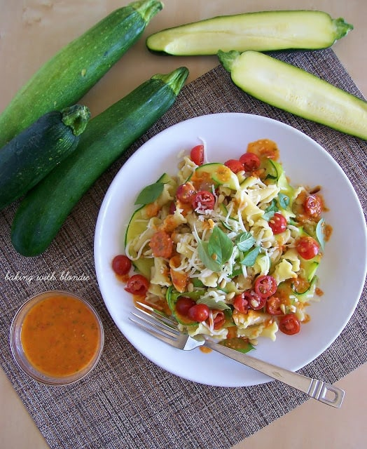 Garden Campanelle Salad with Fresh Tomato Basil Dressing on a white plate with a fork on he plate and zucchini on the side.