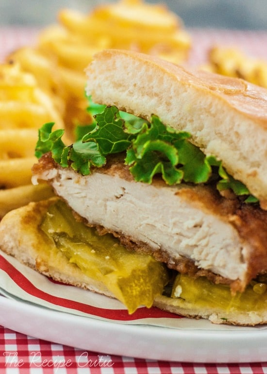 Chicken sandwich with mustard and lettuce with fries.