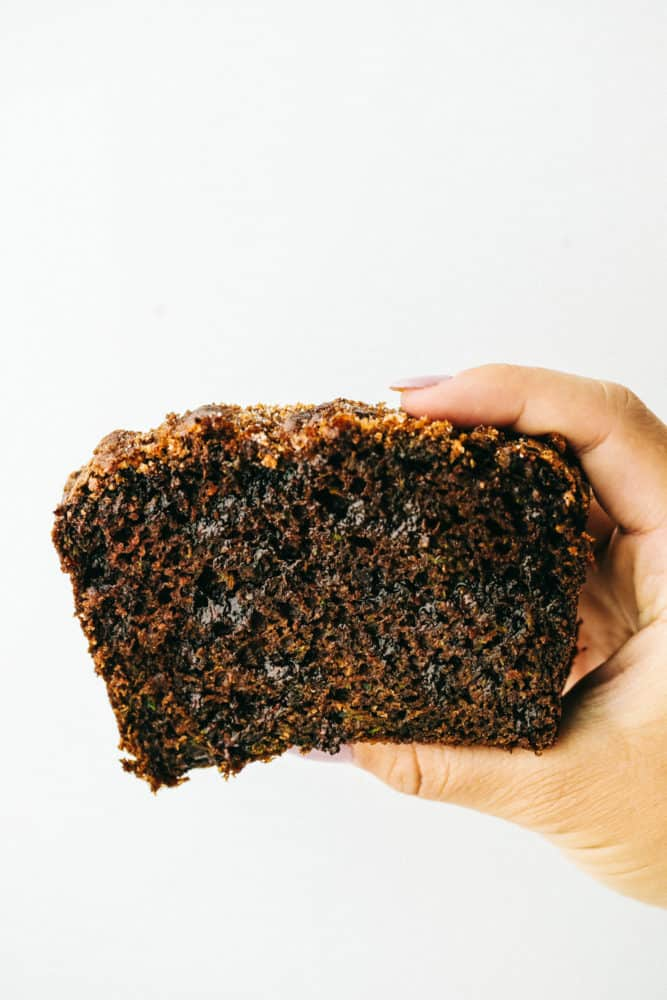 Chocolate zucchini bread held up with a hand with a white background.