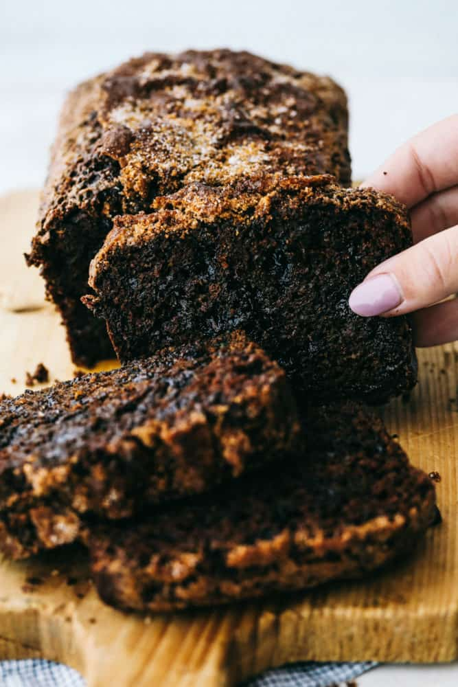 Chocolate zucchini bread sliced in three pieces on a cutting block.
