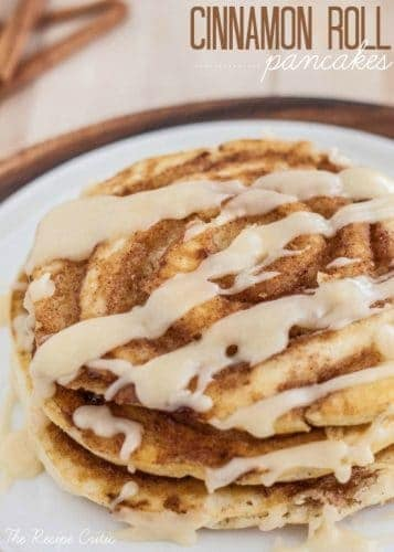 Cinnamon roll pancakes stacked on top of each other with cream cheese glaze drizzled over top with a side of butter.